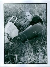Woman relaxing and lying on the grass while picnic.