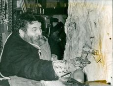 A man carving a big stone using his axe.  Taken - Dec. 1967