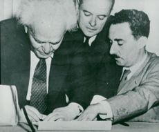 David Ben-Gurion signs the proclamation in Tel Aviv in the presence of his Foreign Minister Mosche Shertok
