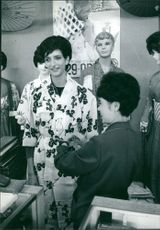 Woman at a tailor shop being assisted in trying out a Kimono.  Taken - Oct. 1964