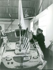 Men checking the boat with flags.