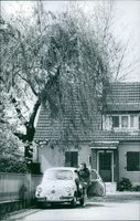 Woman entering inside the car, front view of a house.