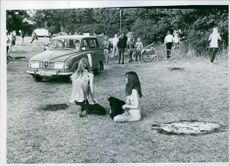Naked woman siting with friend in the park during Festival. 1970