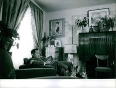 Man from The Lao Royal Family siting in the home.