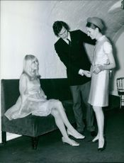 Man checking new dress of woman, another woman looking towards them.