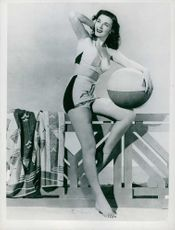 Marguerite Chapman posing in a short skirt and a crop top, holding a ball.