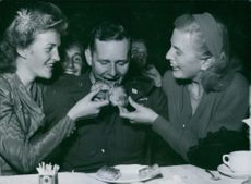 Women feeding a man and smiling.