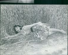 A woman lying on farm field and smiling.