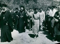 A typical scene in Cyprus; Archbishop Makarios III, carrying the Staff of Office, followed, surrounded and applauded by the people as he arrives for an early morning service.