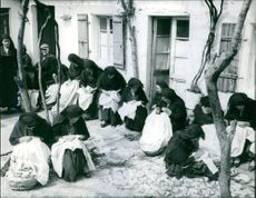 Women sitting together and sewing.