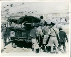 Three suspects being hoisted into an army aptrol truch.