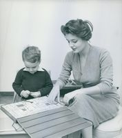 Italian actress Rossana Podesta at home, teaching alphabet to her son Stefano