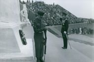 Soldier saluting during an event, other people looking at him.
