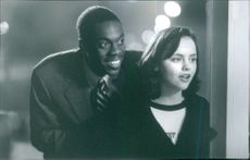Christina Ricci and Doug E. Doug looking towards something and smiling in a scene of film That Darn Cat.  1997