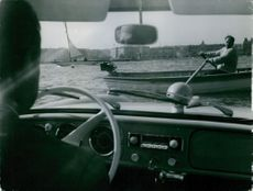A view from inside a car on the coast. The driver watching the men sailing on their boats.