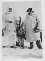 Field Marshal Bernard Law Montgomery in white lamb fur coat standing with a dog.