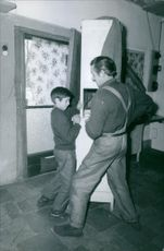 Man with his son pushing a furniture and working. 1969
