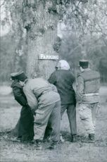 A photo of a four man in a parking looking for something behind the tree.