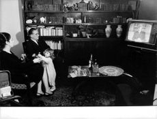 Paul Charrier sitting with woman,child and watching tv.