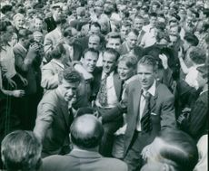 """A popular person being lifted in the middle of a crowd.  """"Sammy Jakobsson hoisted""""  1954"""