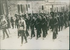 Soldiers holding gun and marching in the street.