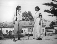 Two Indian women wearing eyeglasses, facing each other.