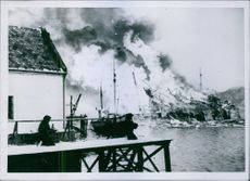 A burning house on Norwegian coast during wartime.  1942.