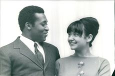 Picture of a black American man and a white American woman, smiling and looking at each other.
