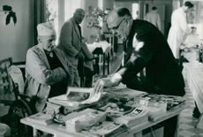Seamen's Institute. Fritz Hallberg receives a number of newspapers by assistant Nils Espelund during his visit to Högalids nursing home