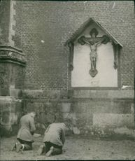 A photo of two man bend their feet and prays in front of Jesus Christ statue. 1915