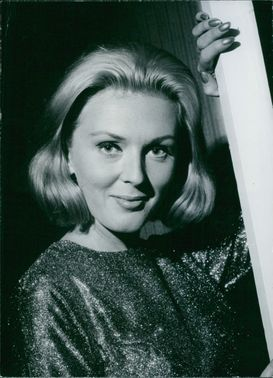 Janie Marden smiling and posing for the camera with her hand resting on a corner of a wall.