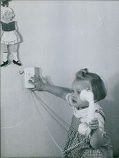 A baby trying to call on the phone.