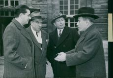 Antoine Pinay standing and talking with men.