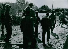 Japanese soldiers who made themselves captured, go to ETL prison camps under the supervision of a U.S. soldier.
