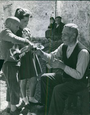 The young boy and girl are giving food to the elderly.