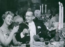 Dan-Axel Broström sitting with wife, Ulla Holm and tossing with her a drink.