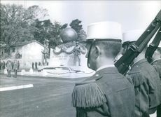 Soldiers and officers standing in attention position, beside the memorial.