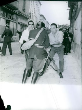 """Two people trying to grab a cop's rifle on the street.  """"Police against communists in Corsica"""""""