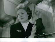 An air hostess standing inside the airplane and looking away. 1962