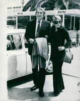 Gregory Peck and his wife Veronique Peck on a parking lot.