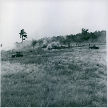 Soldiers firing from military tanks during war.