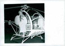 Carroll Baker standing on stair of helicopter.