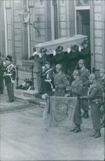 People lifted up a coffin and coming out of the Palace.