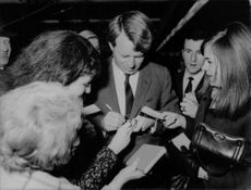 Robert F. Kennedy giving autograph.