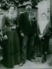 Man and woman posing with their son and smiling.