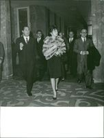 Princess Soraya holding purse and walking with men.