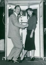Eddie Constantine standing with a woman.