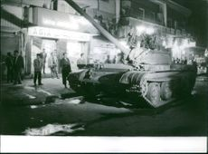 Military tanks and soldiers patrolling at night in the streets of Baghdad.