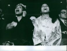 Sugar Ray Robinson's wife and sister cheering for him during his fight.