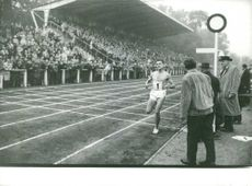 Man running on track, with large audience, October 1962.